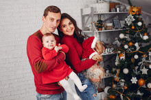 Cute Family Have Fun In Decorating Room. Beautiful Mother With Little Children And Husband. Family In A Red Sweaters