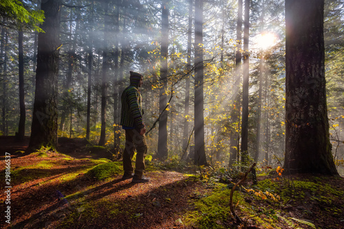 Fotografiet  Adventure Man enjoying the Beautiful Canadian Nature View of the Forest during a foggy morning sunrise