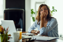 Pensive Woman Feeling Worried While Working On Home Finances.