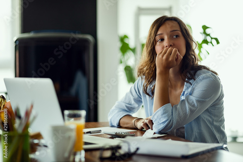 Fotografiet Pensive woman feeling worried while working on home finances.