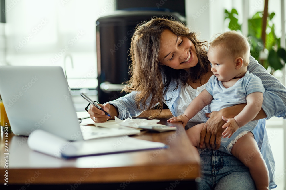 Fototapety, obrazy: Happy mother talking to her baby while working at home.