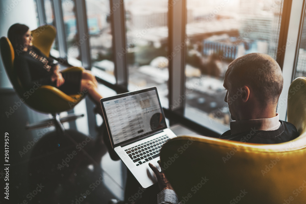 Fototapety, obrazy: A business meeting near the window on the top floor of a luxurious office high-rise with cityscape outside: a man entrepreneur with the laptop and his female colleague aloof in a defocused background