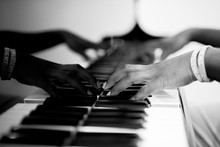 Closeup Shot Of A Person Playing The Piano In Black And White With A Blurred Background
