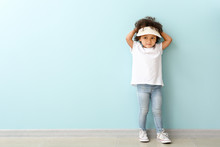 Portrait Of Little African-American Girl Near Color Wall