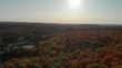 Aerial views of forest treetops and winding river in Gatineau Park, Chelsea, Quebec on a bright and sunny day in Fall.