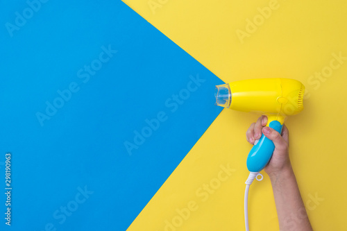 Papel de parede The right hand holds a hair dryer simulating the flow of air on a yellow and blue background