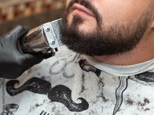 Male in barbershop, close up view. Stylist cutting beaver with clipper. Hands in black rubber gloves. Selective soft focus. Blurred background
