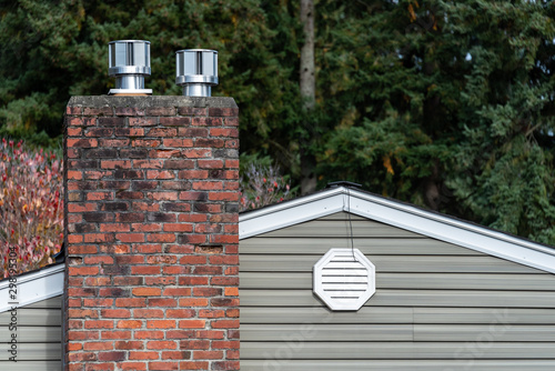 Cuadros en Lienzo Exterior wall of suburban house, old brick chimney with chimney vents, attic fan