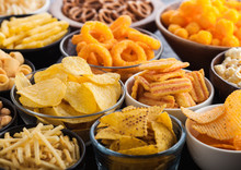 All Classic Potato Snacks With Peanuts, Popcorn And Onion Rings And Salted Pretzels In Bowl Plates On Black Background. Twirls With Sticks And Potato Chips And Crisps With Nachos And Cheese Balls.