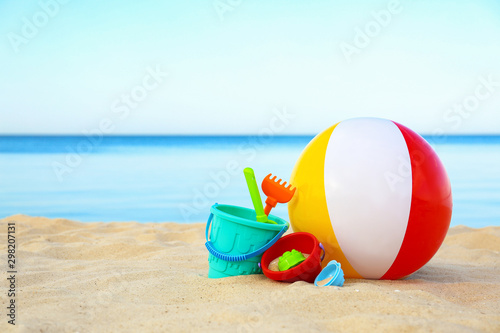 Fototapeta Set of plastic beach toys and colorful ball on sand near sea. Space for text obraz