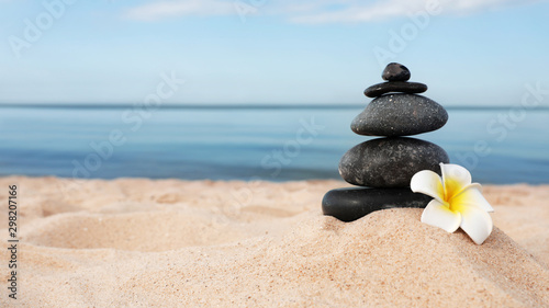 Photo sur Toile Zen pierres a sable Stack of dark stones and flower on sand near sea, space for text. Zen concept