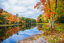 Fall Foliage Colors Reflected In Still Lake Water On A Beautiful Autumn Day In New England