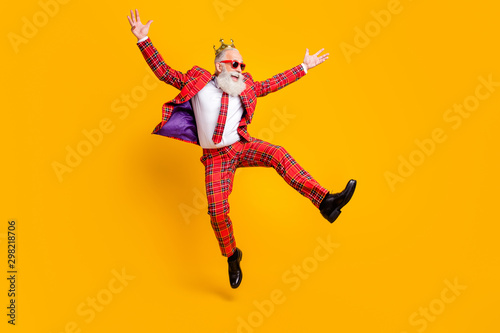Obraz Full length body size view of his he nice handsome attractive cheerful cheery carefree gray-haired man jumping having fun rejoice isolated over bright vivid shine vibrant yellow color background - fototapety do salonu