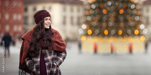 plakat Beautiful joyful woman portrait in a city. Smiling girl wearing warm clothes and hat in winter or autumn. Christmas time with unfocus lights on backgrounde. Copy space