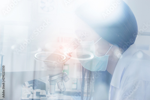 Fotomural  Female scientist doing microscope for chemistry test samples, examining