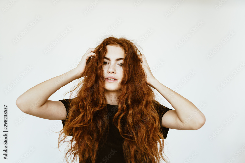 Fototapety, obrazy: Lovely young girl with long curly red hair with freckles on her face in a black T-shirt on a white background holds her hands by her hair and poses