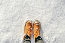 Top View Of Yellow Shoes / Boots Footprint In Fresh Snow. Winter Season.