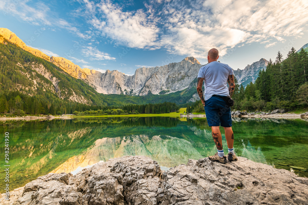 Fototapety, obrazy: Adventure Man with Tattoos Standing at Lake and Looking at Mountains