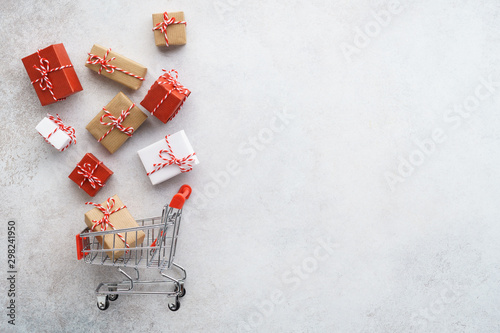 Fotografie, Obraz  Gift boxes flying out of a shopping cart . Light gray background