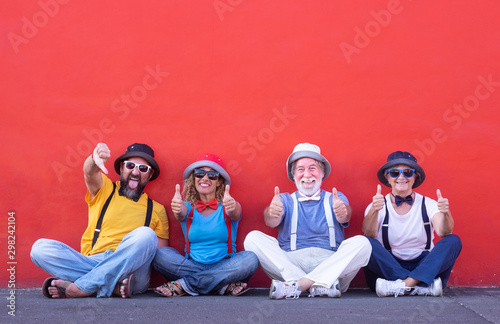 Valokuva  Four people having fun sitting against a red wall