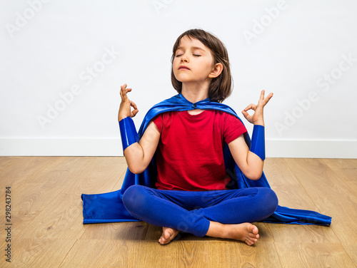 Fotografering proud superhero child practicing yoga and meditation for zen humour