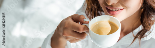 panoramic shot of woman drinking coffee from cup at morning - 298244387