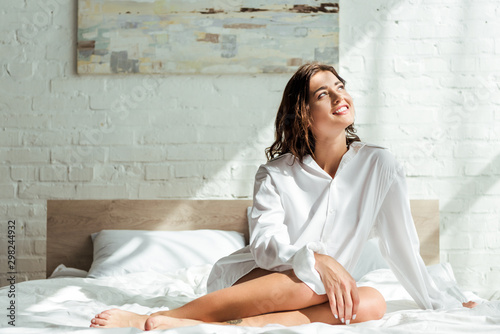 Fényképezés attractive woman in white shirt smiling and sitting on bed at morning