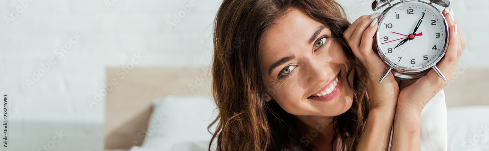Fototapety, obrazy: panoramic shot of attractive woman smiling and holding alarm clock at morning