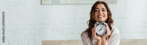 panoramic shot of attractive woman smiling and holding alarm clock at morning Canvas Print