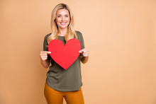 Photo Of Cheerful Positive Cute Pretty Attractive Woman Holding Big Red Heart Wearing Yellow Pants Green Trousers Smiling Toothily Near Empty Space Isolated Pastel Color Background