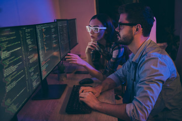 Profile photo of it specialist two guy lady business people sit night chairs coworking watch monitors correct errors bugs writing interface front-end code office indoors