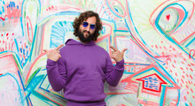 Young Bearded Crazy Man With A Bad Attitude Looking Proud And Aggressive, Pointing Upwards Or Making Fun Sign With Hands Against Graffiti Wall