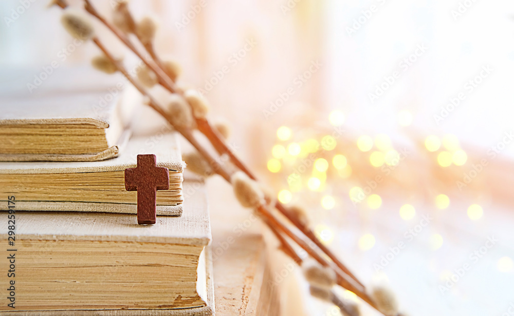 Fototapety, obrazy: wooden cross and books on light abstract background. Orthodox palm Sunday holiday, Easter background. soft selective focus.