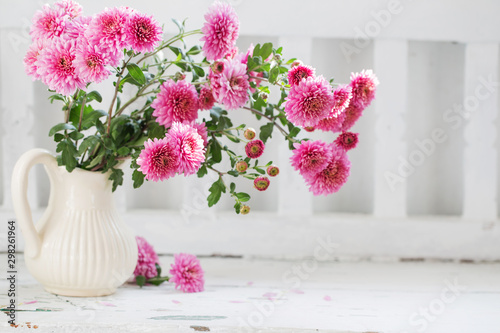 Fotografie, Obraz pink chrysanthemums in jug on old  white wooden bench