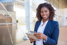Happy Cheerful Customer Paying Online. Young African American Business Woman Standing Outside, Using Tablet, Holding Credit Card. Mobile Banking Concept