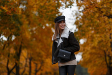 Joyful Young Woman In Stylish Outerwear In An Elegant Hat With A Vintage Bag Stand In The Park And Enjoys The Autumn Scenery. Happy Girl With A Cute Smile Travels On The Forest With Yellow Foliage.