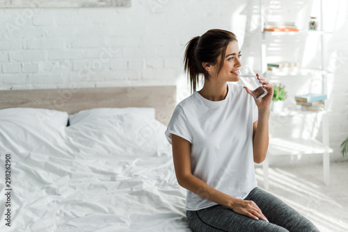Obraz na płótnie beautiful happy girl holding drinking water from glass in the morning