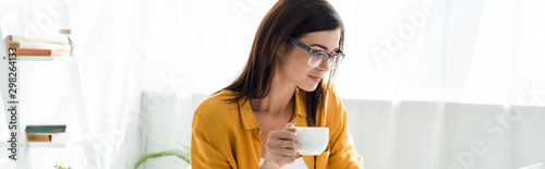 Obraz beautiful female freelancer in eyeglasses holding cup of coffee in home office - fototapety do salonu