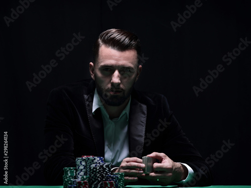 A wealthy man playing poker with the excitement in a casino. - 298264134