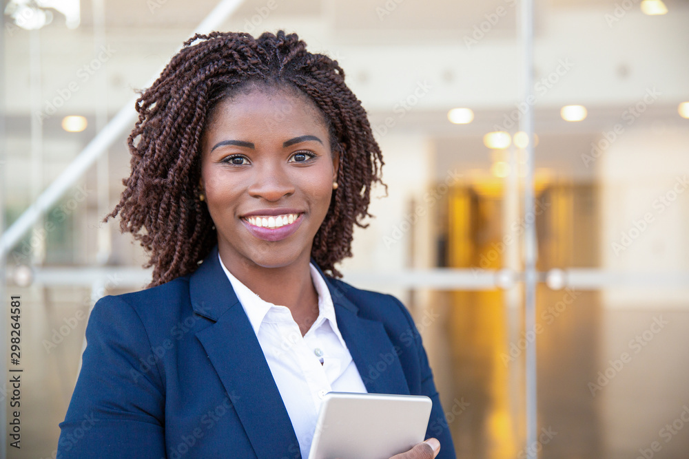 Fototapeta Happy joyful manager with tablet posing outside. Young African American business woman holding and embracing digital device, looking at camera, smiling. Gadget user concept