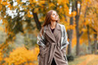 Elegant beautiful young woman in a fashionable long coat with a stylish knitted scarf stands in the park and enjoys the autumn scenery. Trendy girl model walks through the woods outside the city.