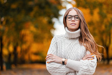 Pretty Cute Young Hipster Woman In A Trendy White Warm Knitted Sweater In Blue Jeans In Fashionable Glasses Posing In The Park On A Background Of Orange-gold Foliage. Attractive Girl Fashion Model.