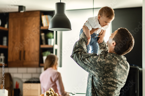 Obraz Playful military man having fun with his small son at home. - fototapety do salonu