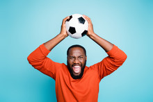 Photo Of Crazy Excited Mixed-race Casual Ecstatic Black Man Raising Soccer Ball Shouting With Goal Grimacing Isolated Vibrant Blue Color Background