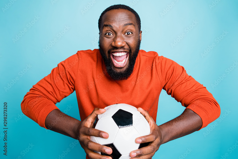 Fototapety, obrazy: Portrait of cheerful excited mixed-race overjoyed ecstatic man holding ball rejoicing in goal of his favorite team isolated over blue vivid color background