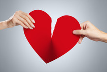 Male And Female Hands Tearing A Red Heart Symbol Of Love In Half