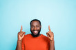 Close up photo of attractive dark skin guy indicating fingers up empty space advising nice low sale prices wear casual orange pullover isolated blue color background