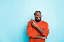 Photo Of Attractive Dark Skin Business Guy Toothy Smiling Indicating Finger To Empty Space Advising Amazing Sales Wear Casual Orange Pullover Isolated Blue Color Background