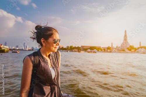 Traveler woman on boat joy view Wat Arun at sunset, Chao Phraya river, Famous la Wallpaper Mural