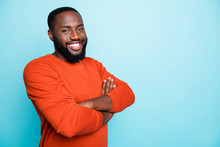 Photo Of Attractive Dark Skin Business Guy Toothy Beaming Smiling In Positive Mood Holding Arms Crossed Wear Casual Orange Pullover Isolated Blue Color Background